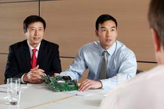 Businessmen discussing circuit board in meeting Stock Photos