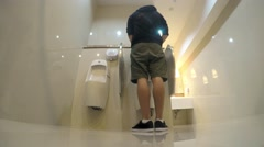 Man Peeing in Toilet with Urinals. 4K Stock Footage