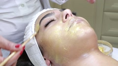 Spa therapy for young girl receiving facial mask at beauty salon  Stock Footage