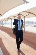 Stock Photo of Businessman talking on city street