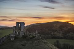 Stock Photo of Landscape image of beautiful fairytale castle ruins during beautiful sunset