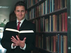 Businessman reading book in library - stock photo