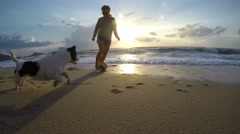 Happy Girl Walking at Sunset at Beach with Dog. UHD Stock Footage