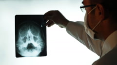 Doctor reviewing hand x-rays print Stock Footage