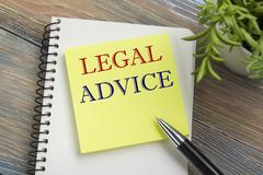 Stock Photo of Legal Advice. Notepad with message, pen and flower. Office supplies on desk