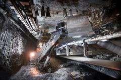 Coalminer operating digger in tunnel of deep mine Stock Photos