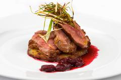 Plate of lamb with leeks and cranberry - stock photo