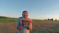 Farmer standing on the wheat field and holding fresh bread Stock Footage