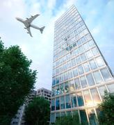Stock Photo of buildings with flying airplane and trees concept business and tourism background