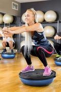 Smiling group training squats on half ball at fitness gym Kuvituskuvat