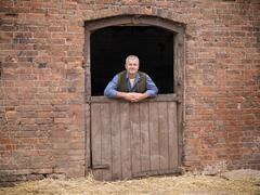 Portrait of farmer leaning on stable door Stock Photos