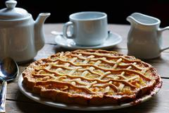 Dish of treacle tart with coffee - stock photo