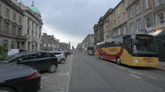Walking and riding bikes on George street, near Joules store, in Edinburgh - stock footage