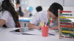 4K Happy group of children working at their desks in school classroom Stock Footage