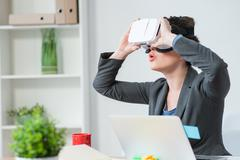 Beautiful young businesswoman is using eyewear device Stock Photos