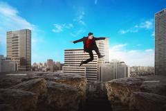Asian business man jumping over broken road Stock Photos