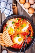 Shakshuka. Fried eggs with tomato, paprika and parsley - stock photo