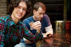 Two men at bar, one holding shot glass Stock Photos