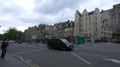 Driving and riding bikes on Grassmarket street in Edinburgh Stock Footage