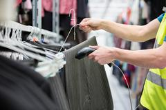 Man checking pair of trousers in warehouse Stock Photos