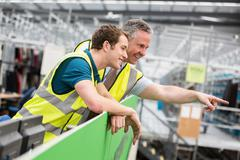 Two men in warehouse, one pointing - stock photo