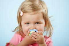 Girl with pacifier in mouth Stock Photos