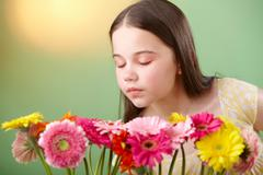Girl sniffing flowers - stock photo