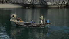 fishermen on a traditional vietnamese boat pouring water out of the leaking boat - stock footage