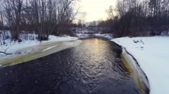 Winter landscape. Sunset at river and forest. Aerial footage. Low altitude. Stock Footage