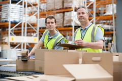 Two men checking stock in warehouse Stock Photos
