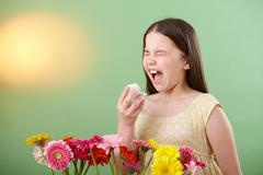 Girl with flowers sneezing Stock Photos