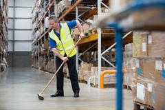 Man sweeping warehouse floor with broom Stock Photos