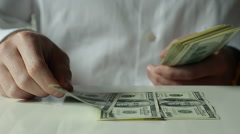 Closeup of a Businessman Lays Out Hundred Dollar Bills on the Table Stock Footage