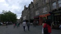 Walking and sitting at outdoor restaurants in Grassmarket square in Edinburgh Stock Footage