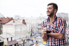 Cheerful guy is feasting his eyes upon town - stock photo