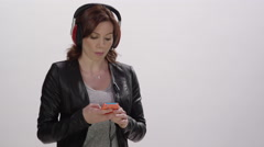 Stock Video Footage of Digital Lifestyle - Young woman using headphones on her smart phone