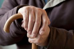 Senior man with walking stick, close up Stock Photos