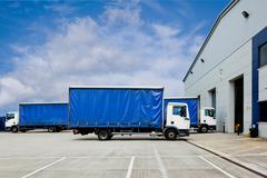 Trucks parked outside distribution warehouse - stock photo
