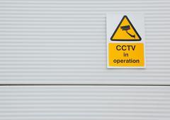 Stock Photo of Surveillance camera sign on warehouse door