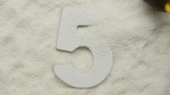 Five. Wooden number in sand. 4K UHD video. - stock footage