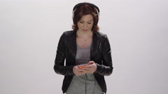 Digital Lifestyle - Young woman using headphones on her smart phone - stock footage