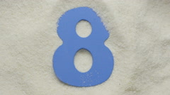 Eight. Wooden number in sand. 4K UHD video. - stock footage