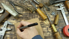 Man draws a draft. Indicates dimensions. Vintage tools on background - stock footage