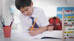 4K Portrait of happy little boy in classroom writing in exercise book Stock Footage