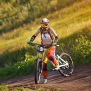Extreme sports - young woman riding downhill bike - stock photo