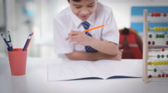 4K Portrait of happy little boy in classroom writing in exercise book - stock footage