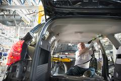 Worker fitting headliner in car in car factory - stock photo