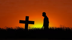 Man kneeling down by gravesite at sunset Stock Footage