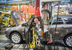 Car assembly workers fitting doors to cars on production line in car factory - stock photo