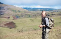 Hiker wearing backpack on hillside - stock photo